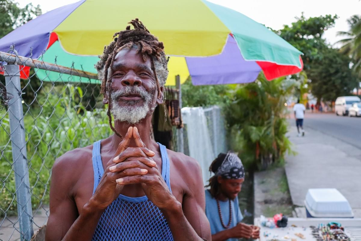 Rasta elder smiling in Saint Lucia while a man sits at a table and makes jewelry