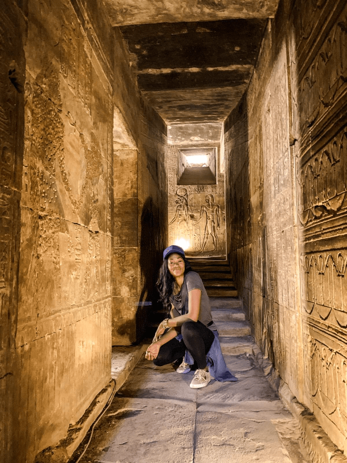 Brit Thompson in the halls of Edfu Temple of Horus with Egyptian hieroglyphics in Aswan, Egypt