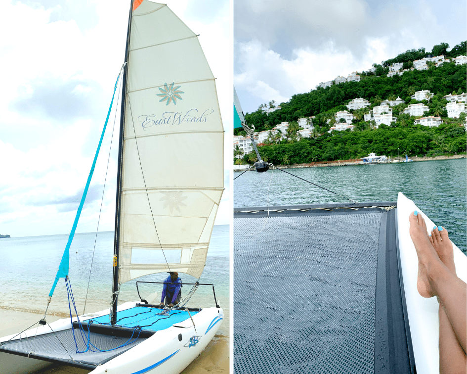 Small East Winds sailboat on the beach and feet resting on a boat off the St Lucia bay in the Caribbean Sea