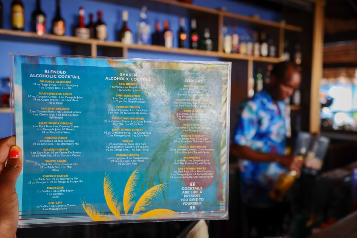 A drink list at a bar in the Caribbean with a waiter mixing drinks at East Winds Resort in Saint Lucia Caribbean