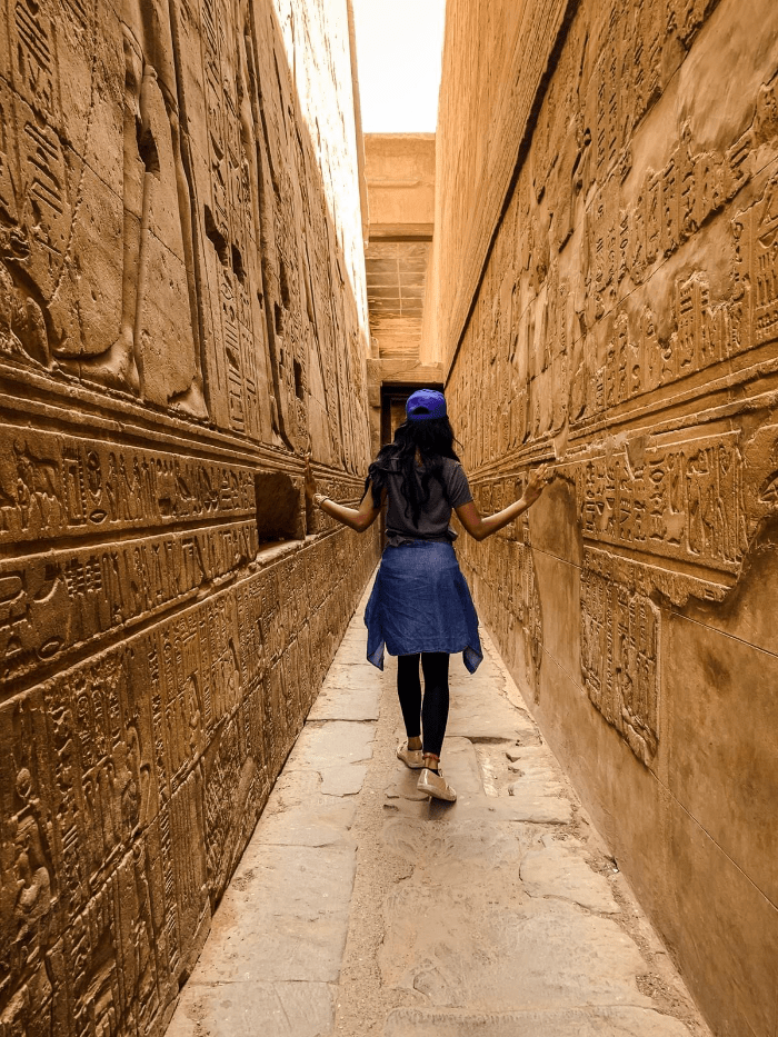 Brit Thompson walking down the corridors of hieroglyphics in Edfu Temple of Horus in Aswan, Egypt