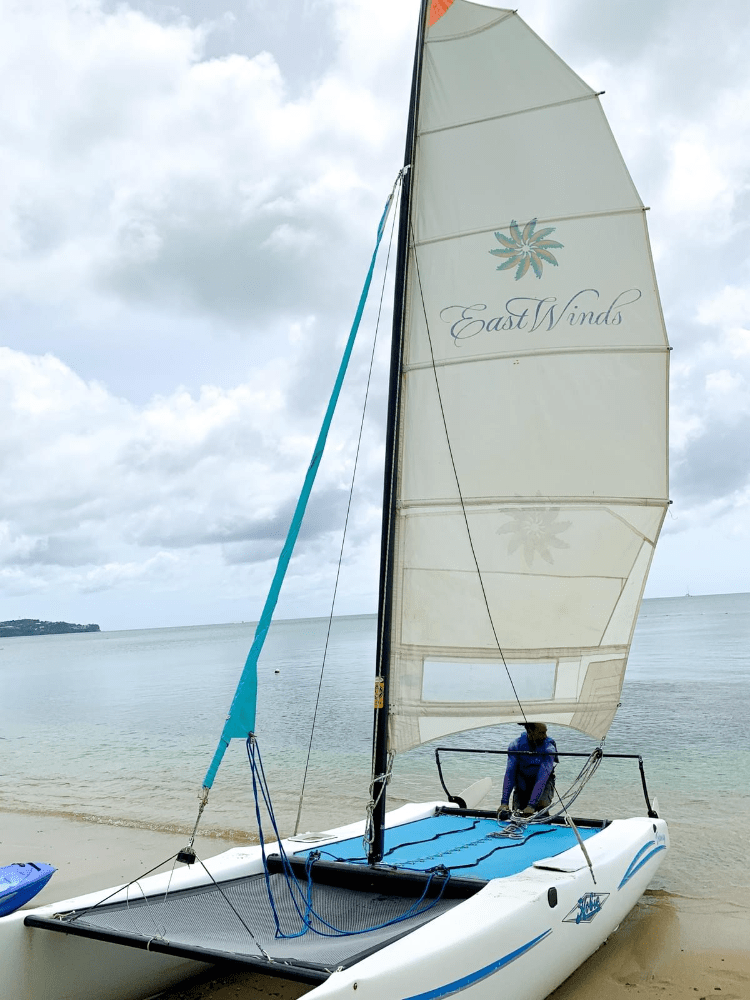 Man pulling a sail boat catamaran into the Caribbean Sea in Saint Lucia at East Winds Resort