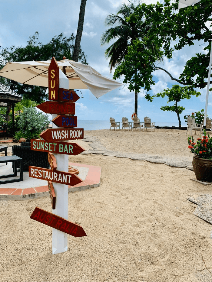 Direction and Restaurant and bar Sign pointing to the beach with sand and beach chairs at East Winds resort in Saint Lucia Caribbean Island and blue sky