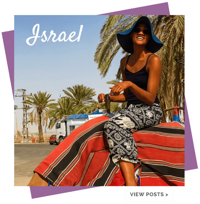 black girl in hat on camel with red and black cover in israel