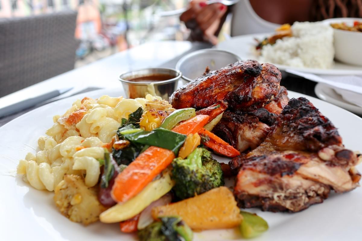 Traditional Caribbean recipes of vegetables, macaroni salad, and chicken from Matthew's Rooftop Restaurant in Castries in Saint Lucia