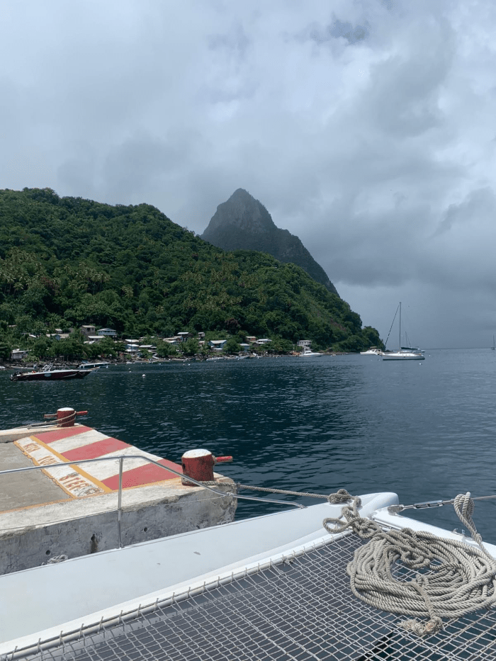 A docked catamaran in front of the Pitons with sailboats and green rainforests and boat rope and netting