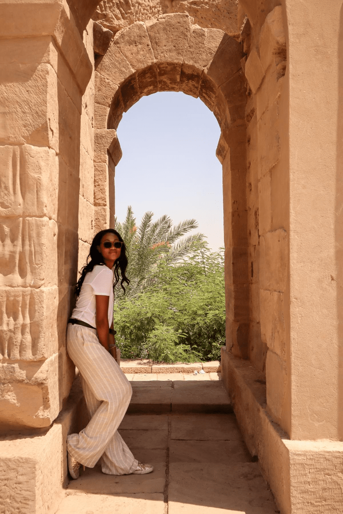 Brit Thompson hiding from the sun at the Temple of Philae in Egypt