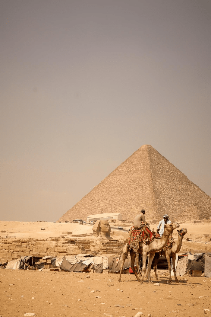 Men relaxing on camels near the Great Sphinx and the pyramid of Giza in Cairo Egypt