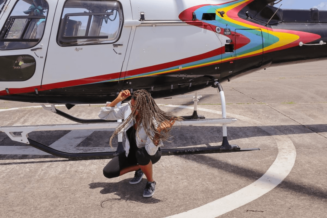 Woman bending down tossing hair in front of a helicopter pad