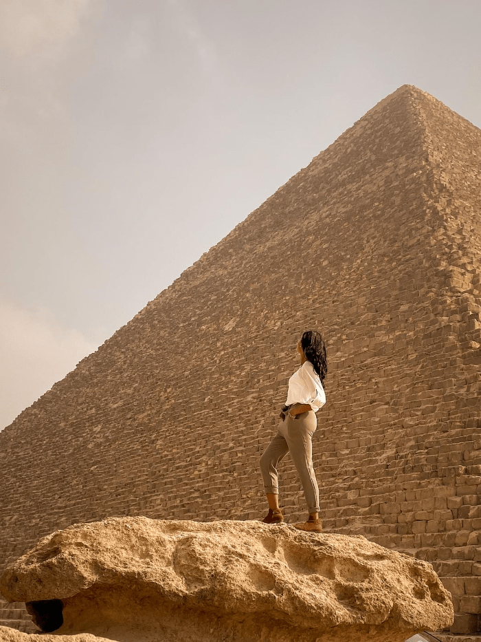 Brit Thompson mounting a boulder in looking back at the largest of the Great Pyramids of Egypt