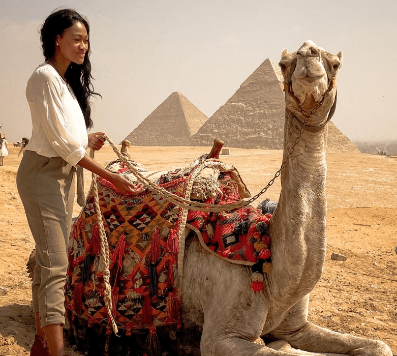 Brit Thompson standing with a smiling camel sitting down in front of the Great Pyramids of Egypt in historic Cairo