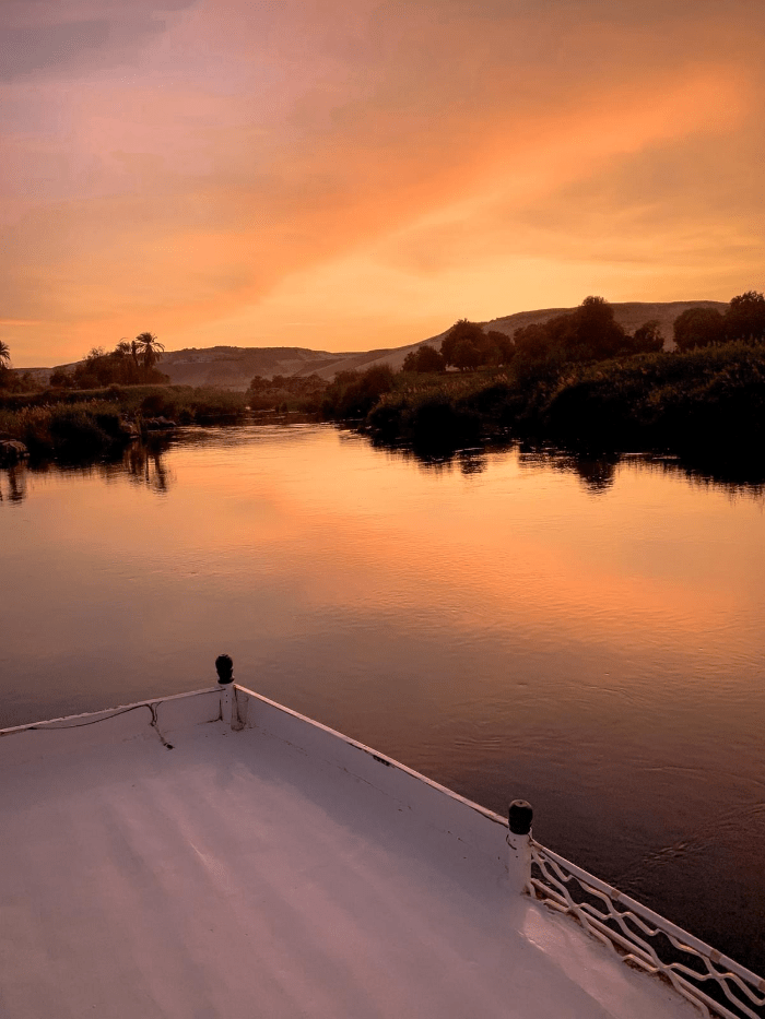 The front of the boat sailing down the Nile River in Aswan, Egypt at sunset phot taken by Brit Thompson