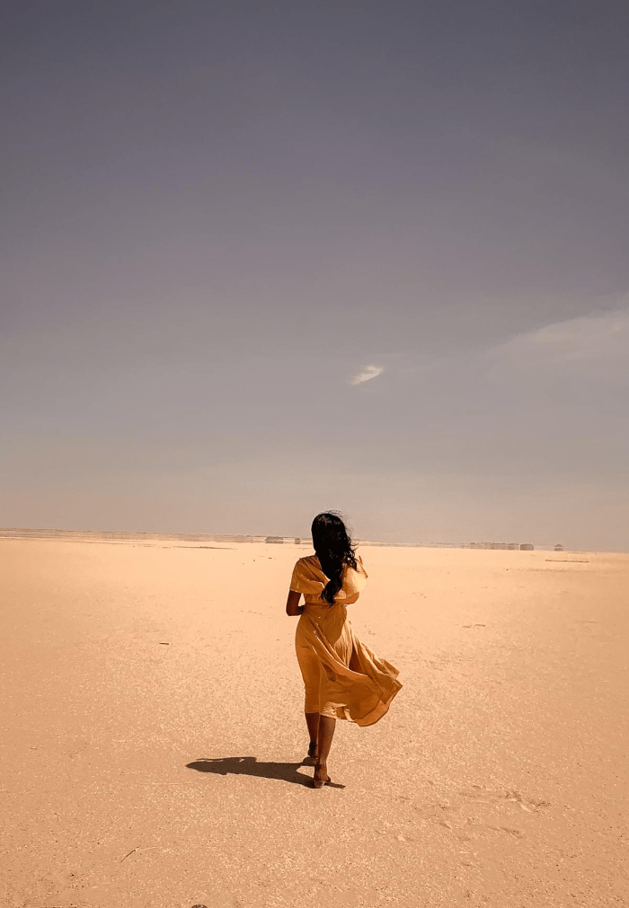 Brit Thompson walking towards a mirage  in the Egyptian desert in a yellow dresss