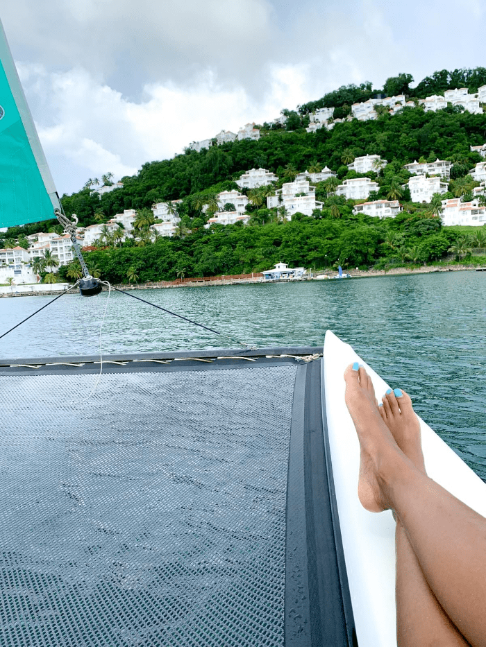 feet up on the sailboat as it cruises the Caribbean Sea towards the coast of Saint Lucia and the cliffside villas
