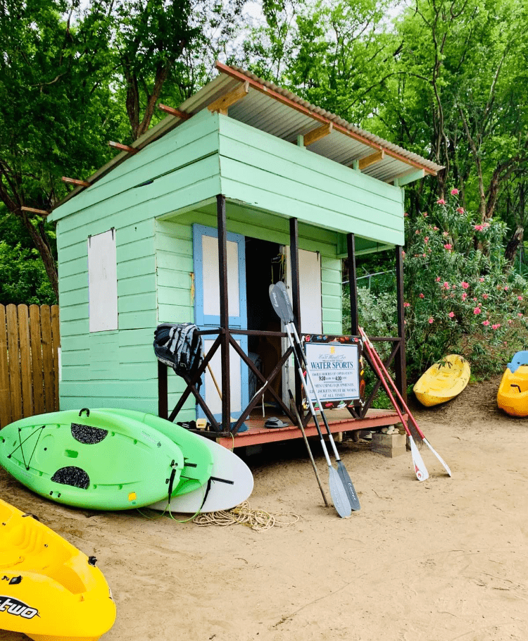 The Water Sports shed at the Caribbean Island All-Inclusive Resort East Winds in Saint Lucia with paddles, canoes, wetsuits, and gear out front