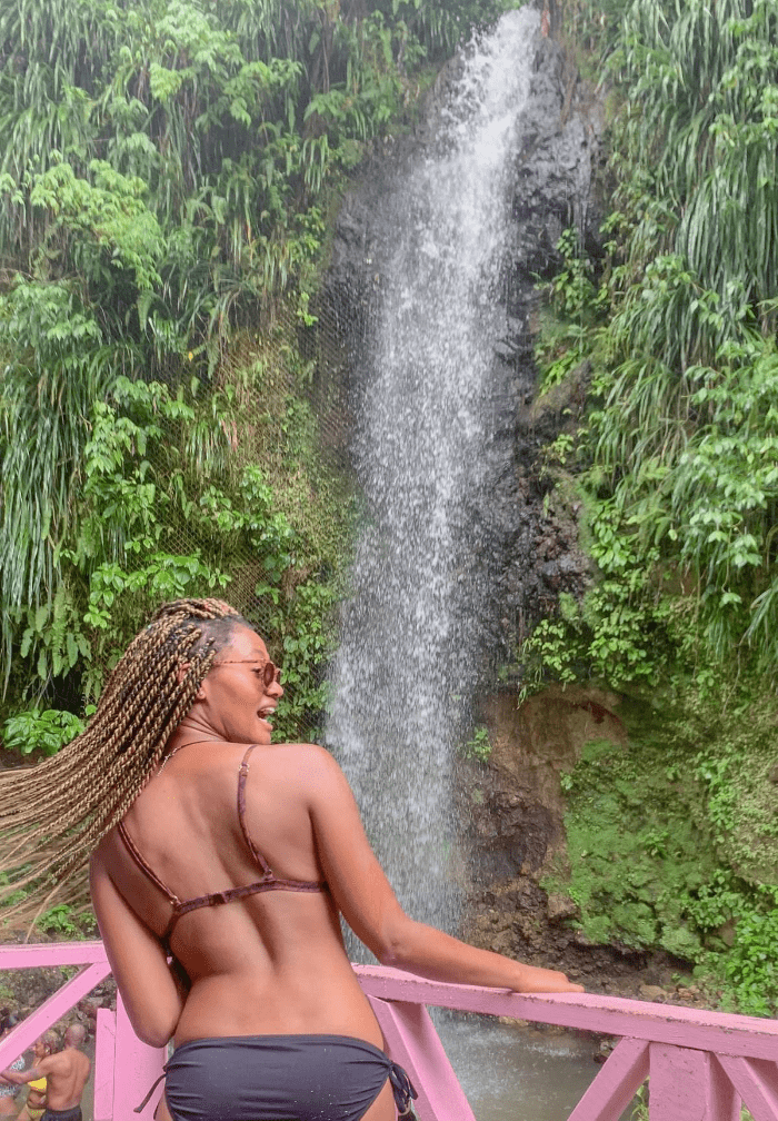 Black girl hair toss in a bikini in front of a waterfall in Saint Lucia