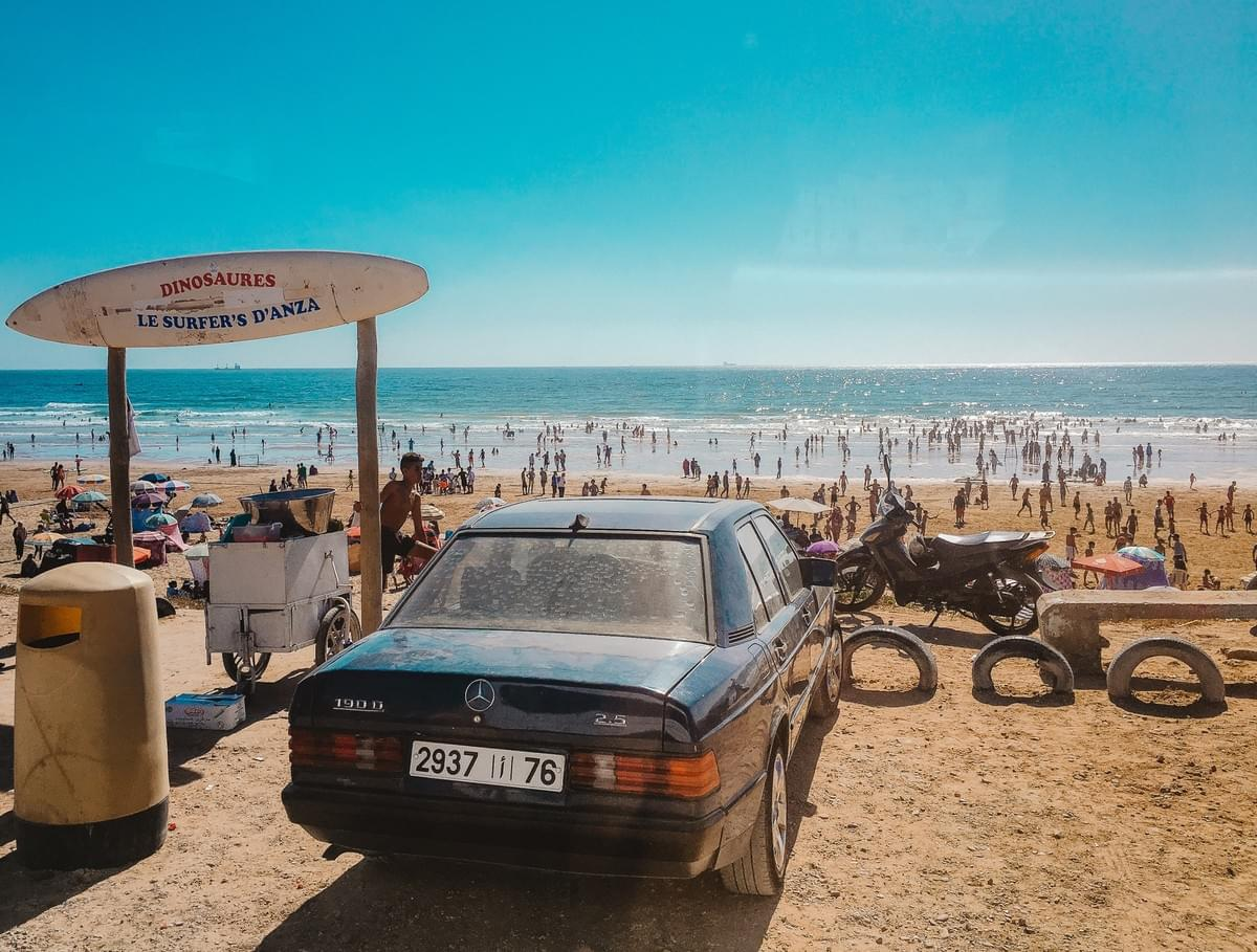 Vintage mercedes, motorcycle and tires parked at the beach next to a trashcan and display surfboard that reads dinosaures le surfer's d'anza with people swimming in the ocean at taghazout bay, agadir, morocco