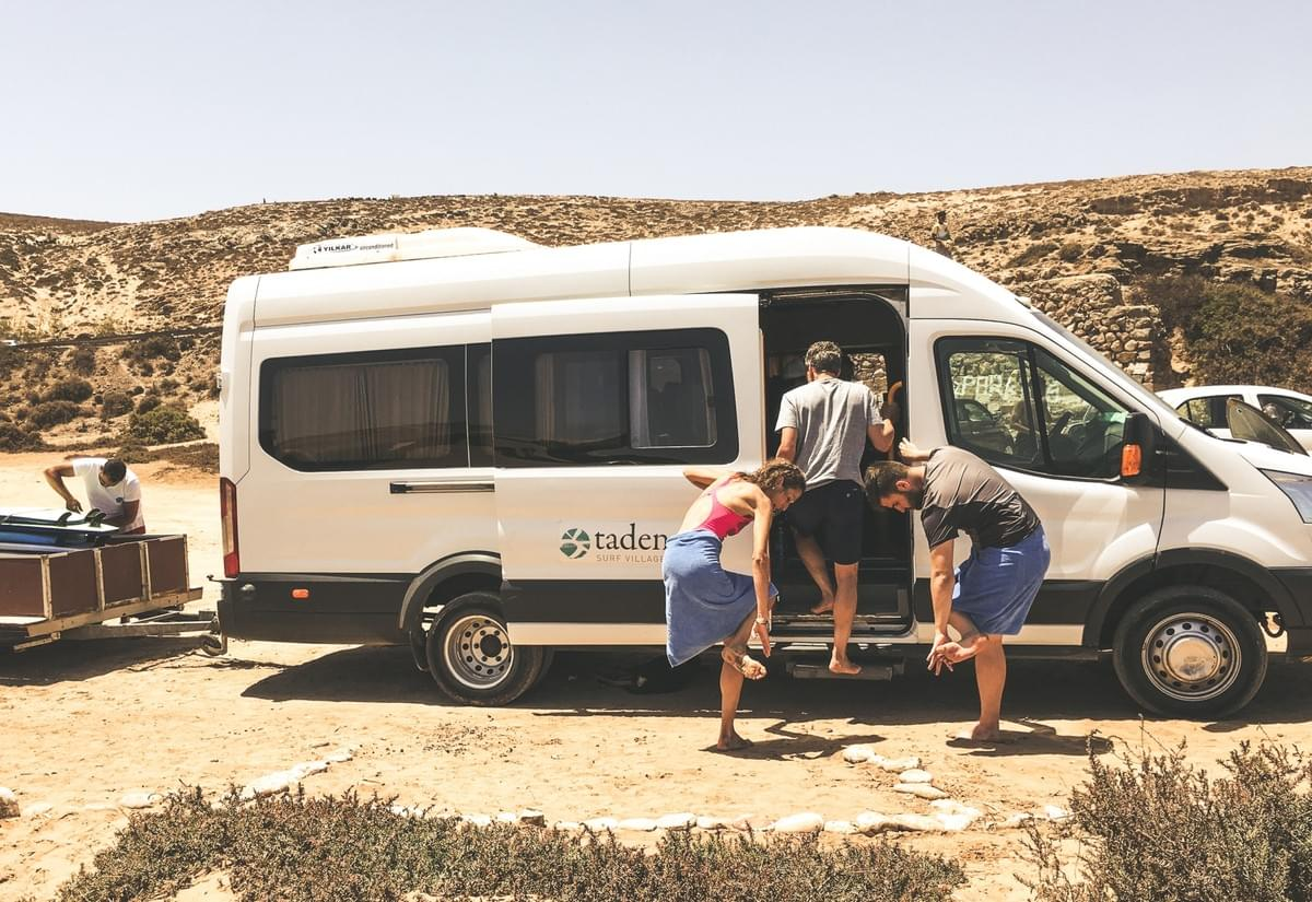 A man unloading surfboards in the back of a truck and people dusting sand of their feet infant of a tadenga shuttle van parked in Tamri, morocco