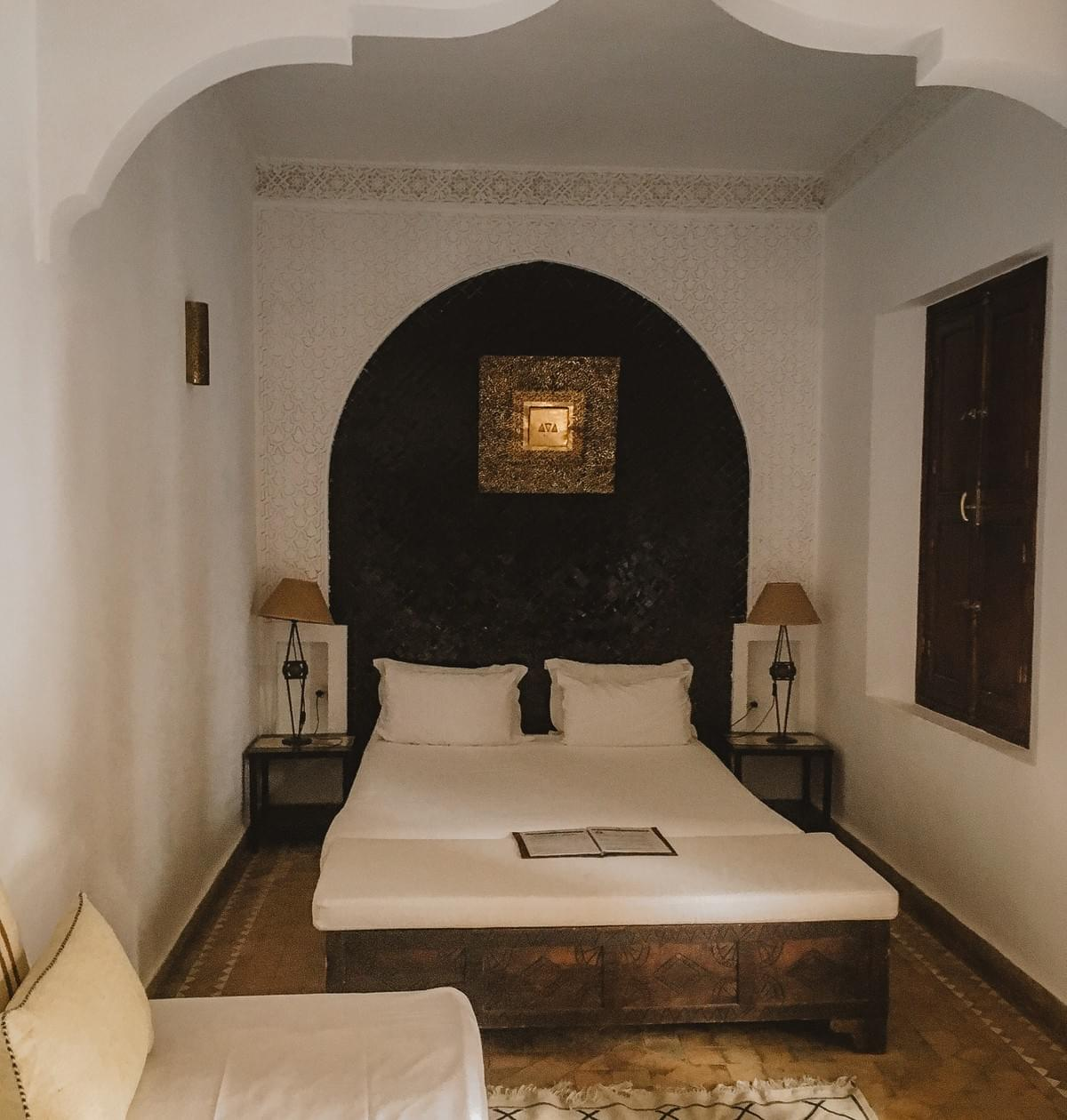 A room with white couch and pillows, a double bed with side tables and lamps on either side. with Moroccan detailing, crown molding, and gold center photo and closed window