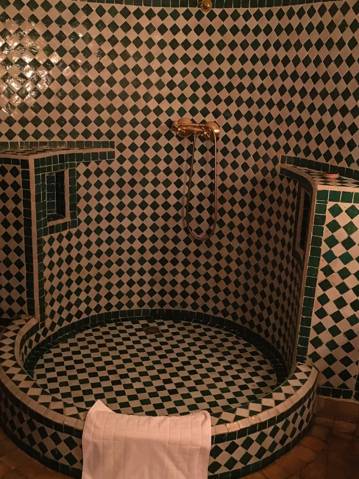 A green and white checkered tiled traditional moroccan bath with a gold faucet