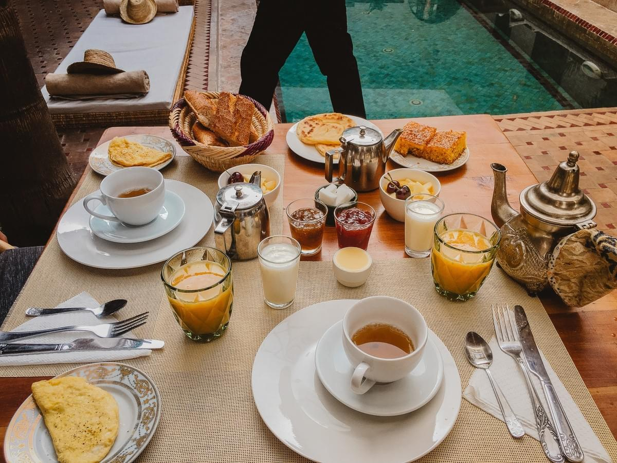 Breakfast table with half omelet, silverware, cups of orange juice, jams, pastries, milk, cups of nana tea and an antique moroccan metal tea pot with a mat, hat and pool in the background