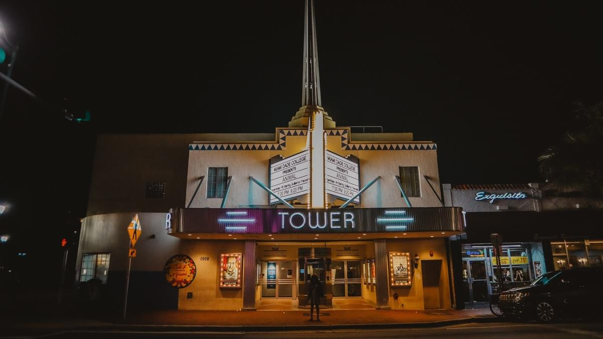 Tower Theater in Miami at night with neon lights and marquee and girl standing alone