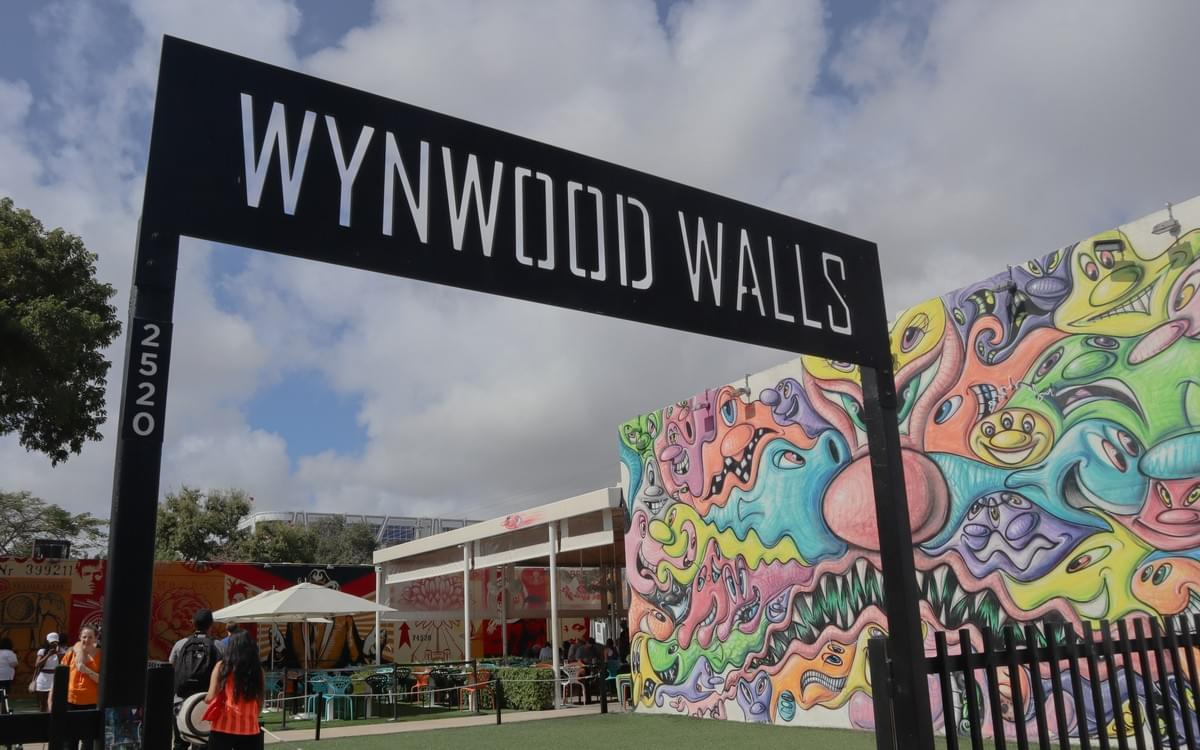 Wynwood Walls entrance gate with street art and clouds in the background