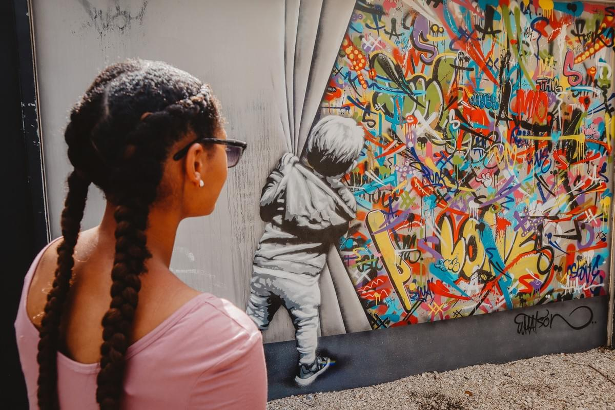 Girl in french braids and sunglasses staring at street art of a boy pulling back curtain of graffiti at Wynwood Walls