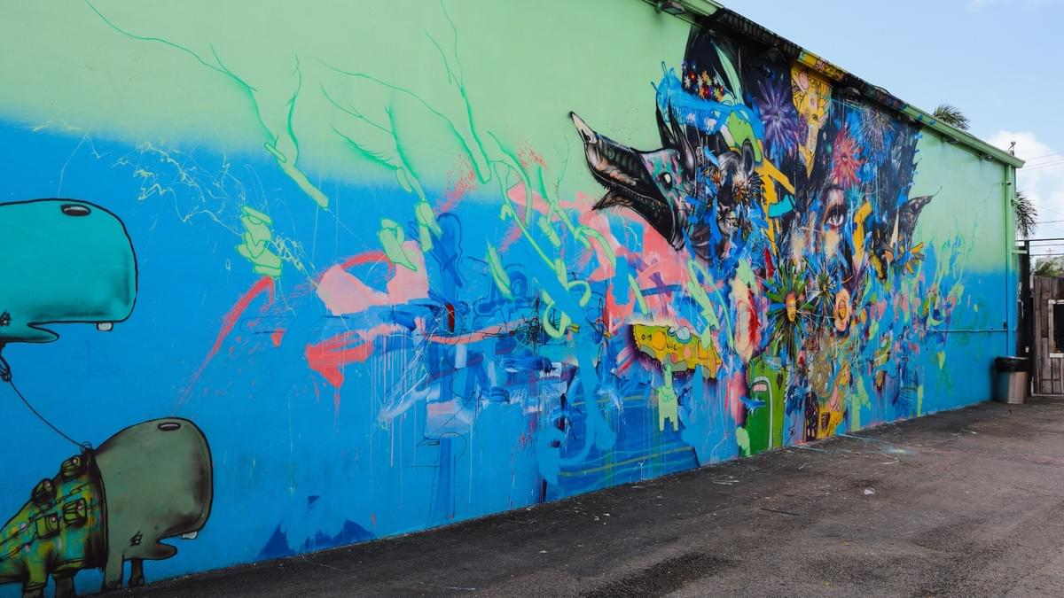 street art mural with blue and green wall with animals coming out of it