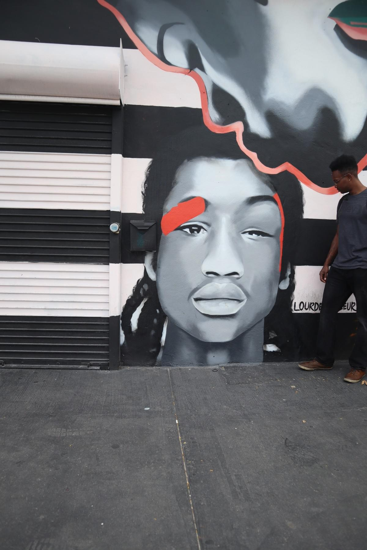 Wynwood walls street art of woman kissing the heads boy with braids with man walking by
