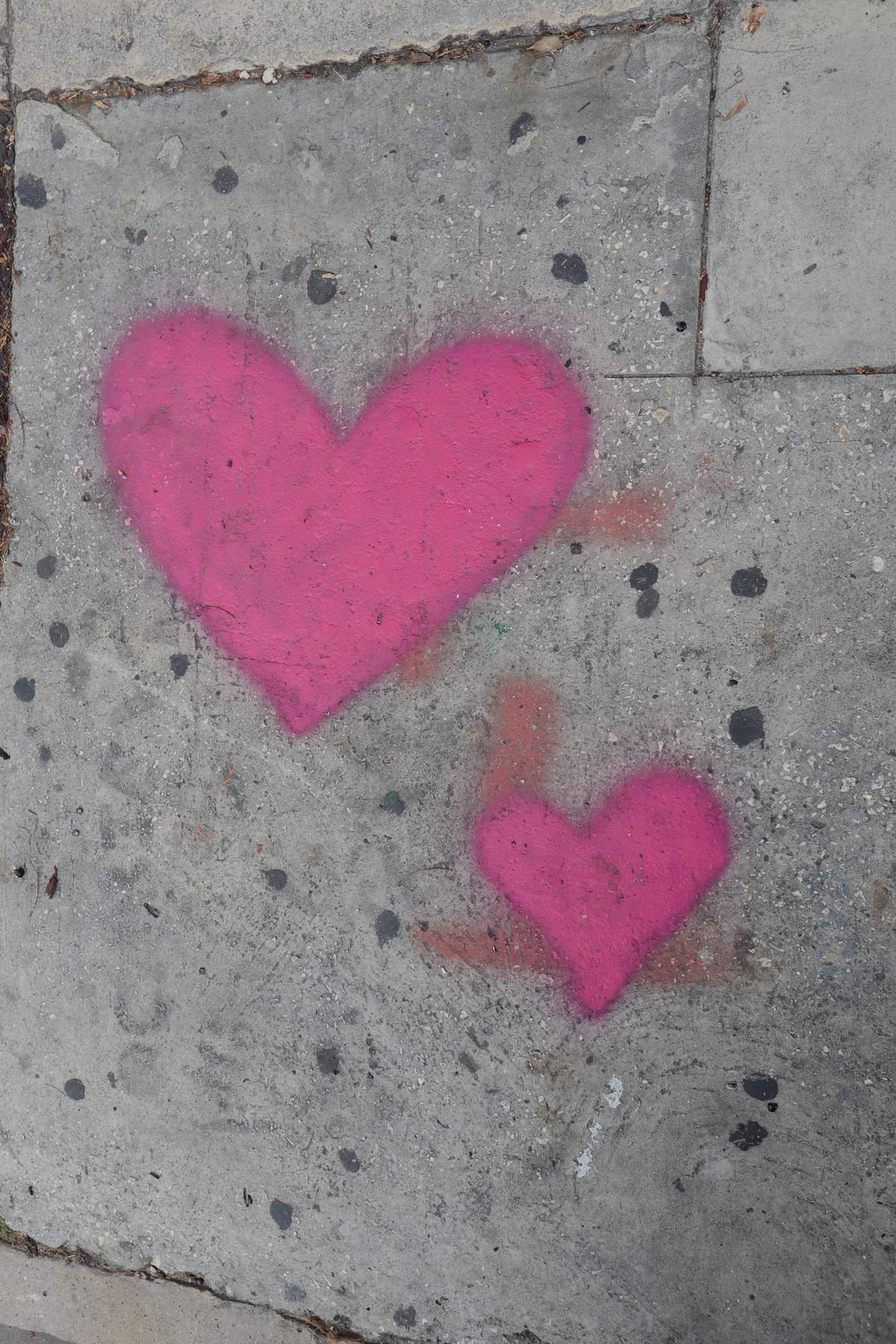 two pink stencil graffiti hearts on the side walk near wynwood walls in miami