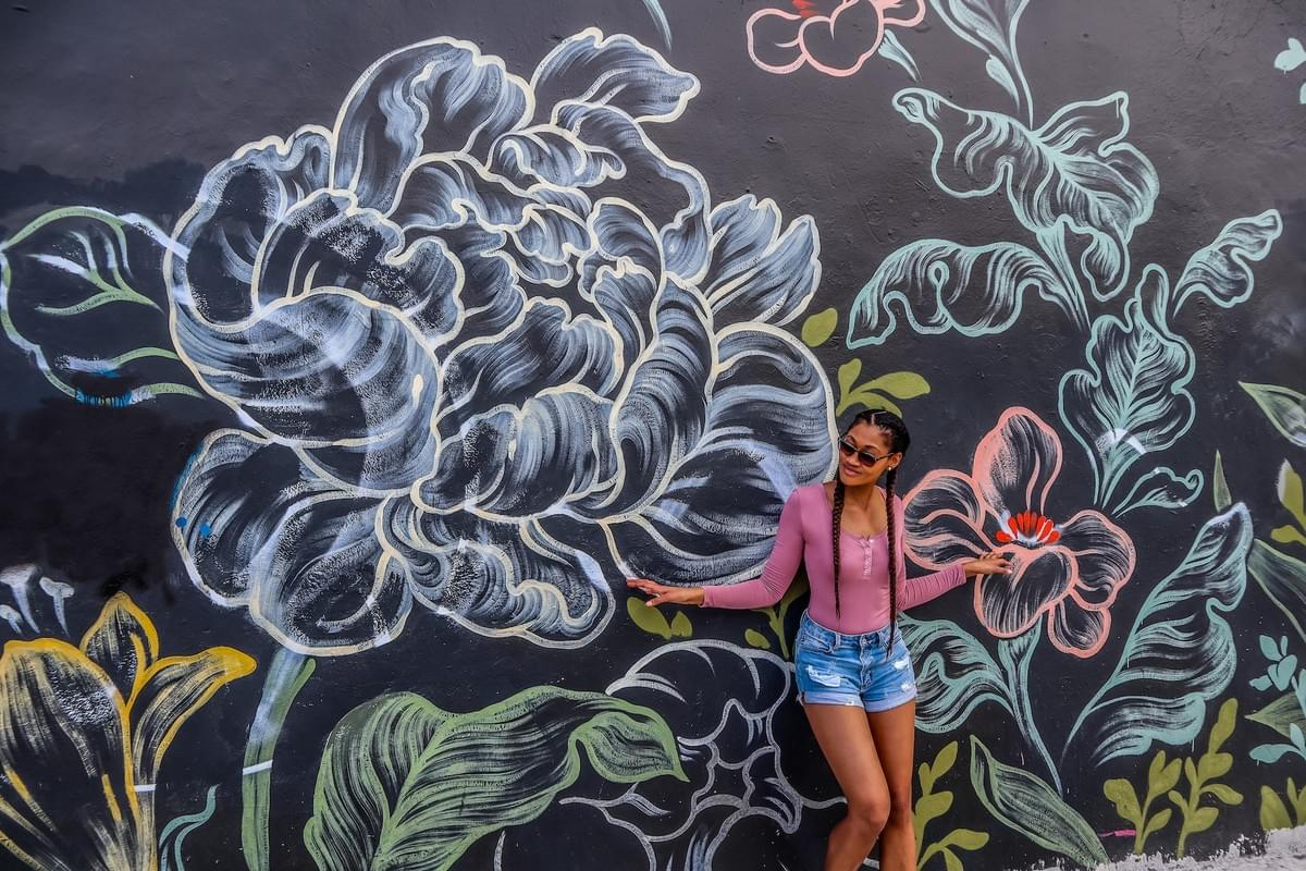 Girl with long french braids and sunglasses leaning against chalkboard graffiti wall at Wynwood Walls in Miami