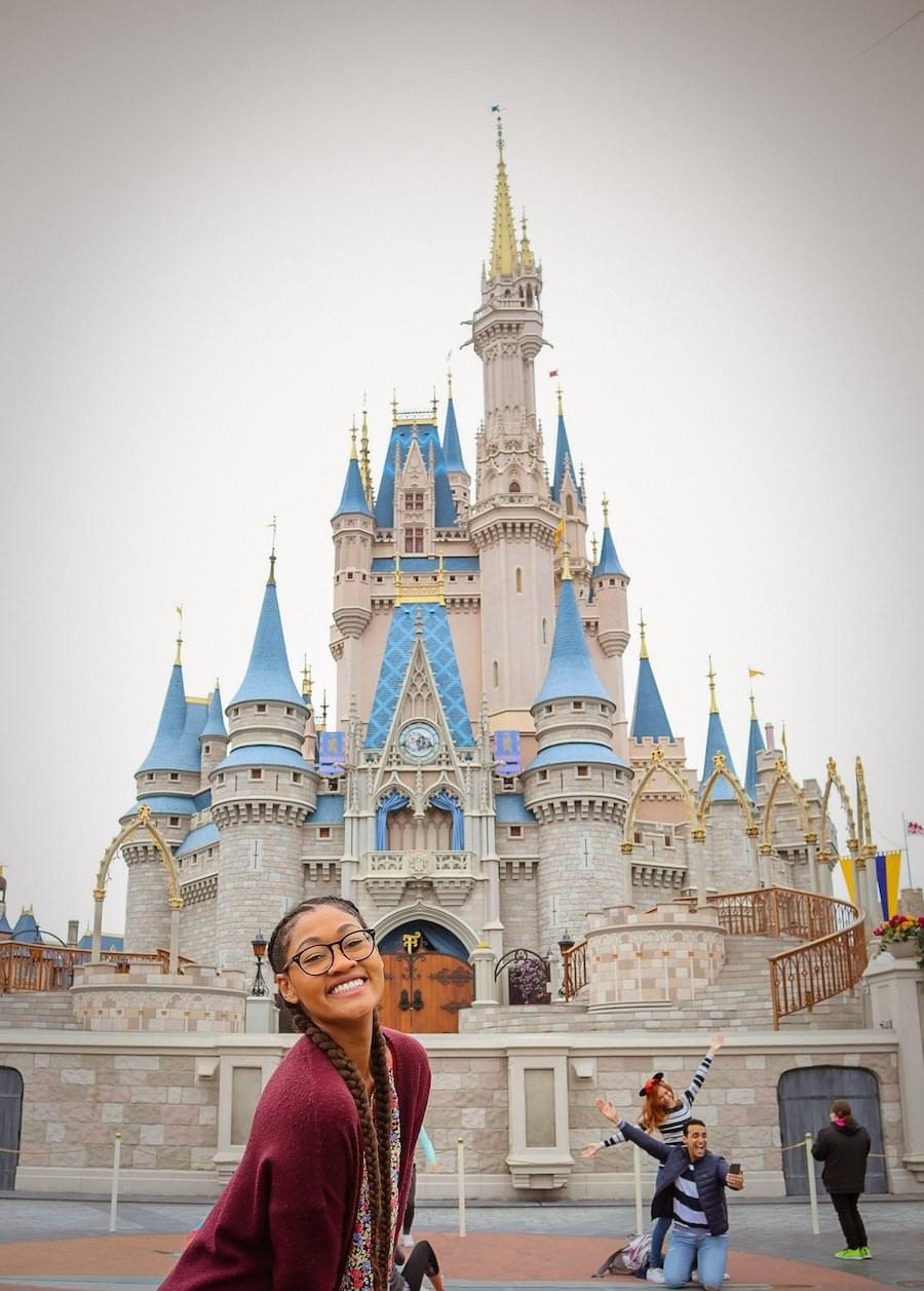 French braids brown black girl posing in front of the magical kingdom cinderella castle at Walt DisneyWorld Magic Kingdom