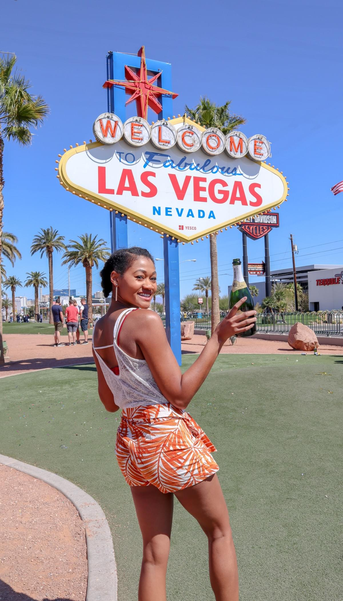 Natural hair brown black girl holding champagne bottle in front of Welcome to Las Vegas sign