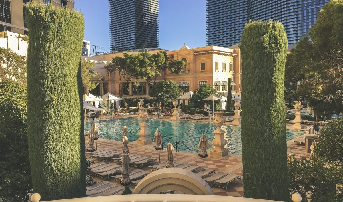 A view of the Bellagio pool hotel facade with plants, trees, lounge chairs, umbrella, cabanas, in the winter