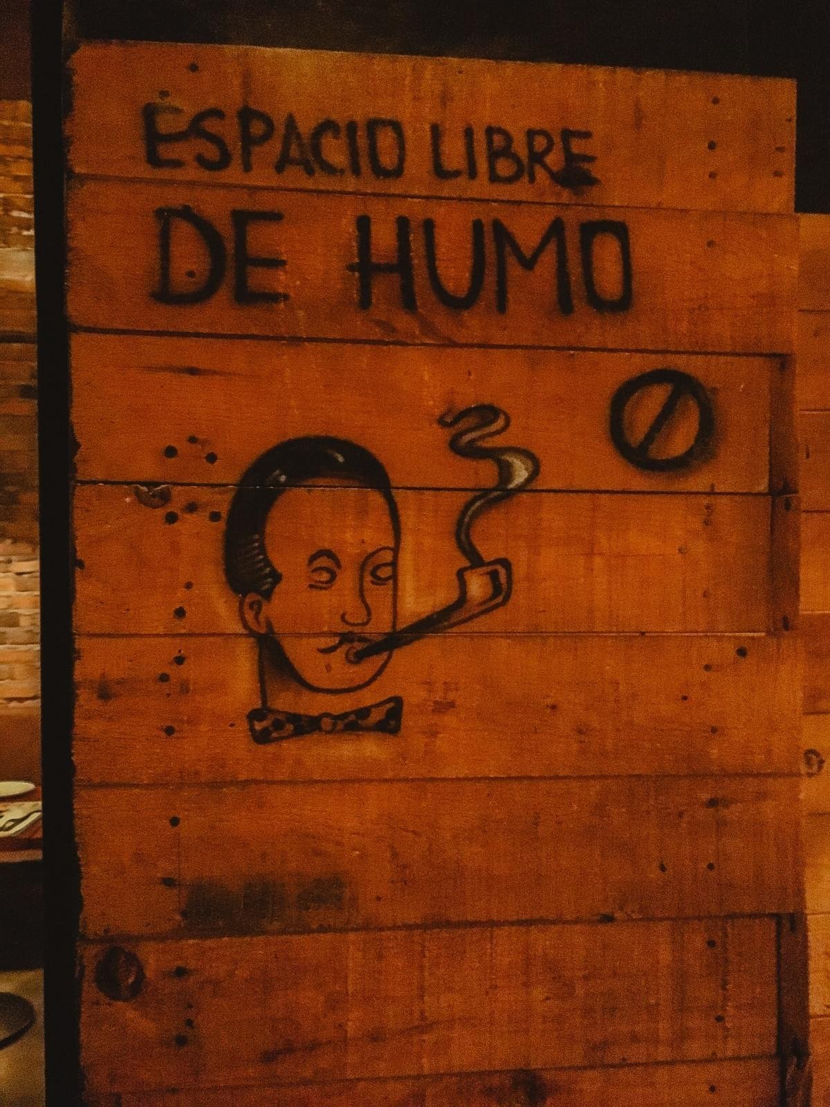 street art sign that reads espacio libre de humo above a circle with a line and a hipster man with bowtie and mustache smoking a cigar