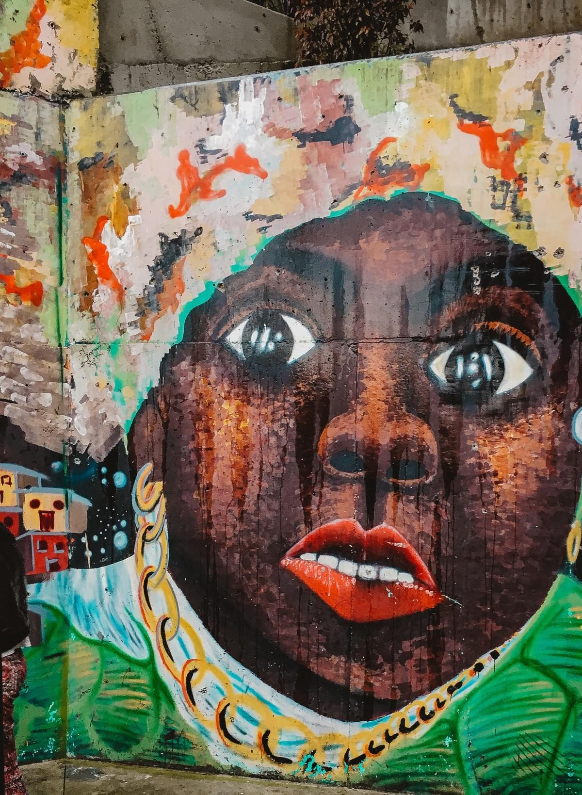 Street art of black woman with red lips and white teeth, gold chain and head wrap in comuna 13 Commune 13 San Javier