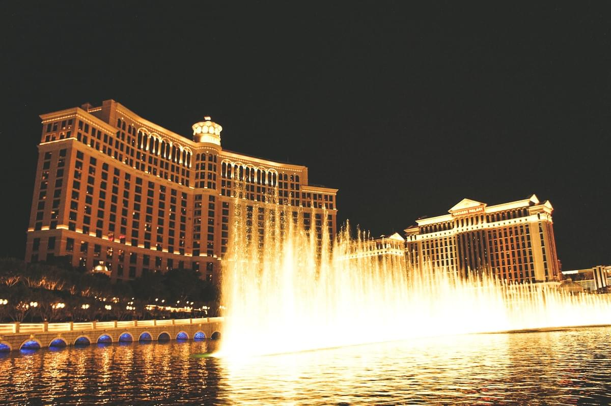 Lights and bellagio water fountain at night in front of the best hotel facade