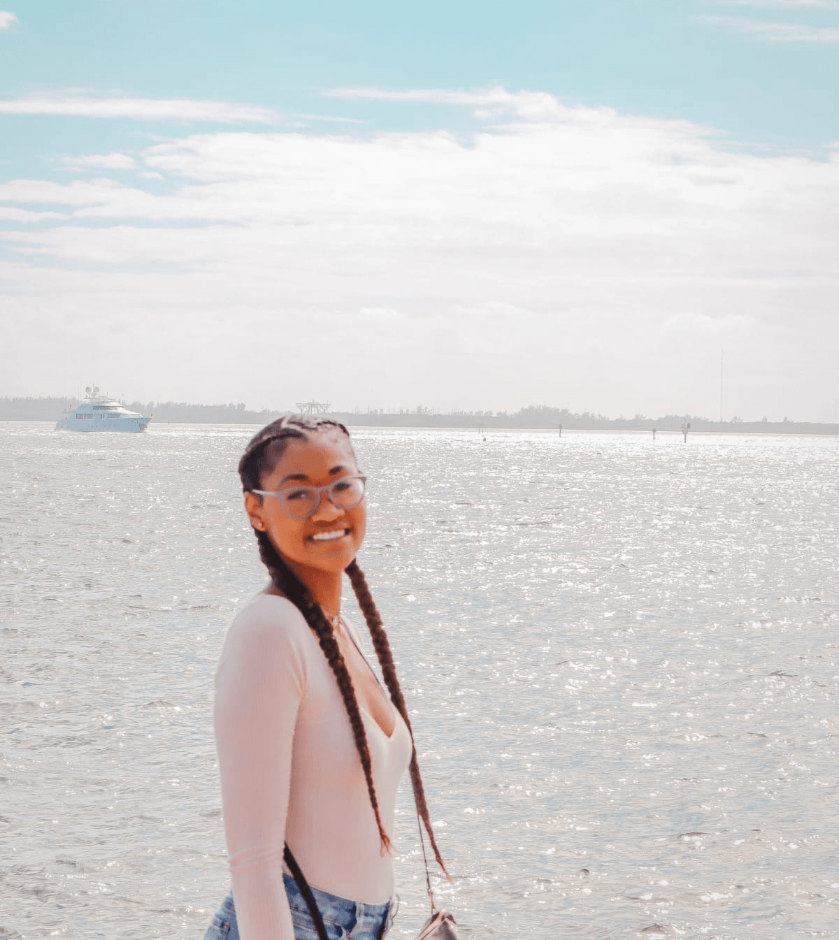 Black girl with  french braids smiling by the ocean with boat in the background