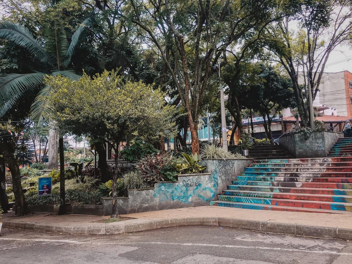 street art on concrete stairs next to trees in the park in el poblado in medellin