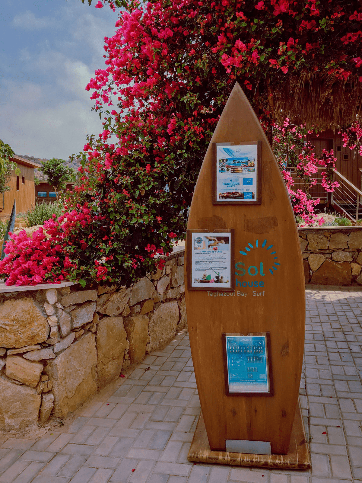 sol house taghazout bay resort surf board display with an activities and events calendar surrounded by pink flowers, stone, and bungalows