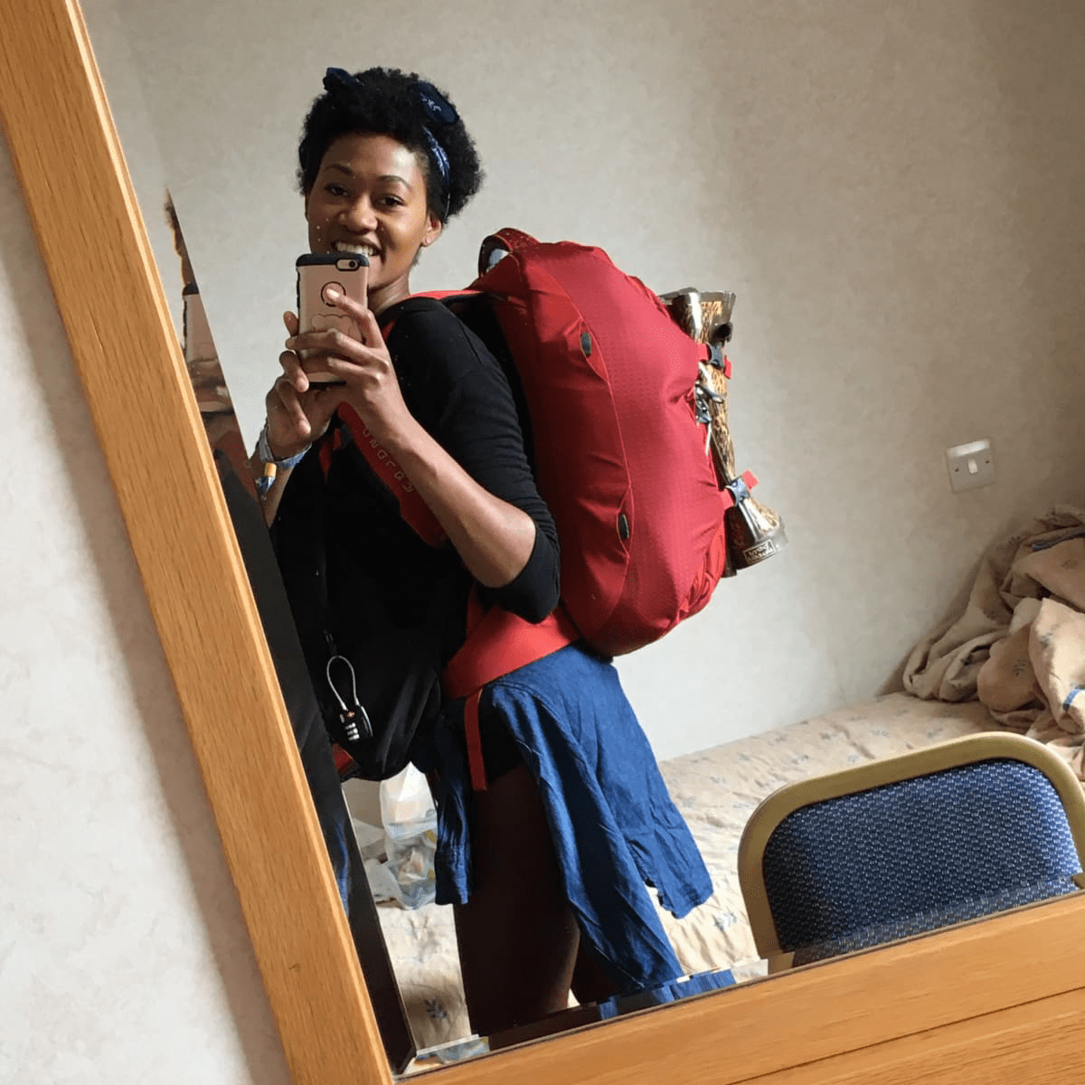 Black natural hair backpacker taking selfie in the mirror of a hotel room wearing a red Osprey backpack and a black bag