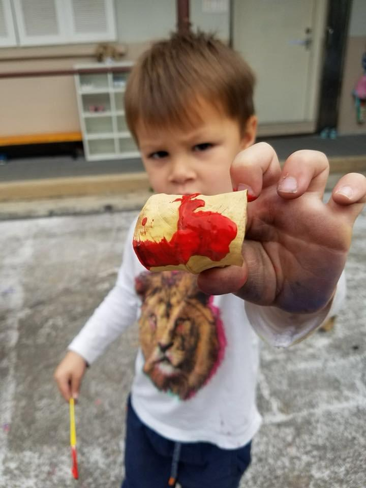 A child shows off the leaf he painted in bright red ready for Chinese New Year