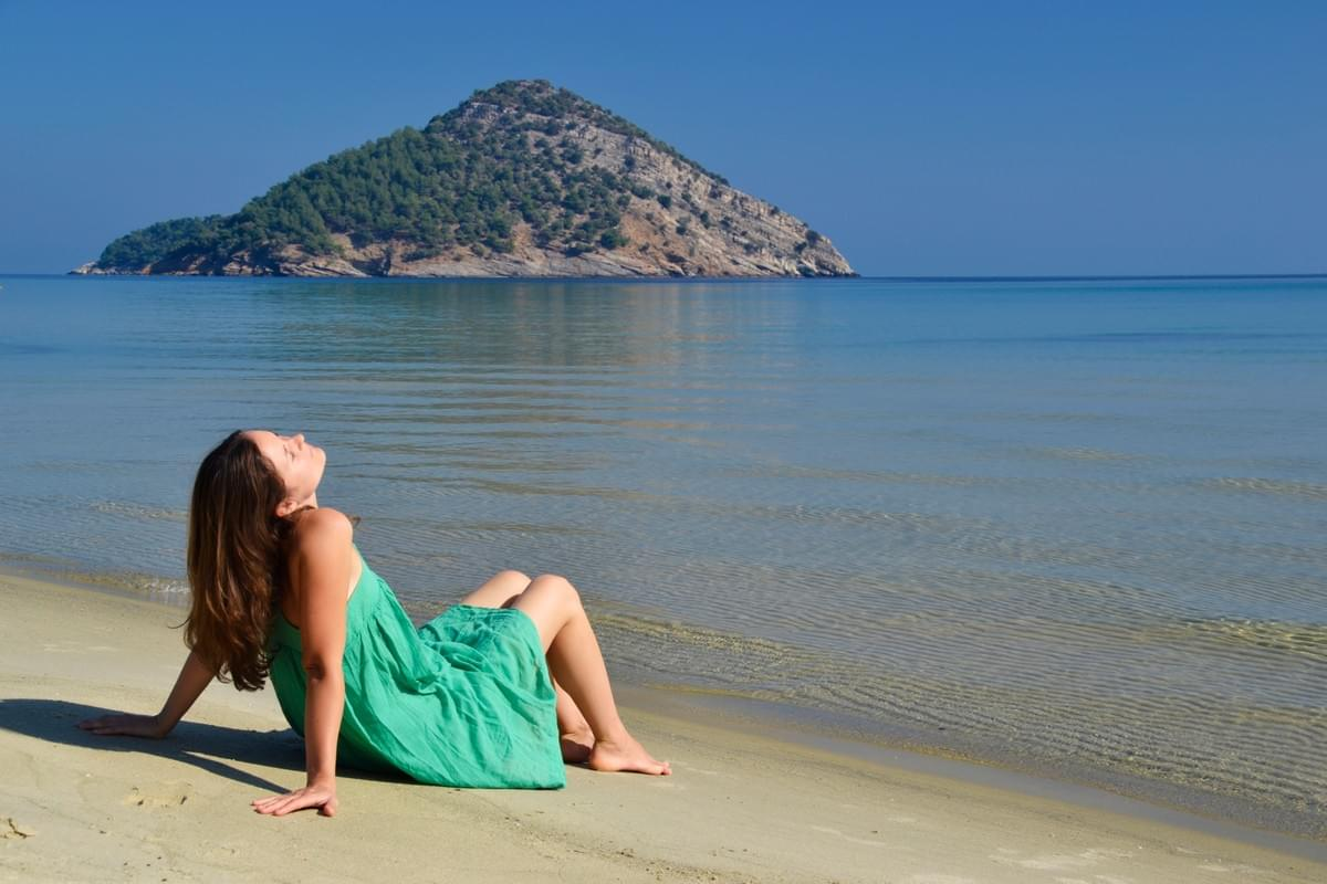 Yoga of You photo:  Lady relaxing on beech in Greece.