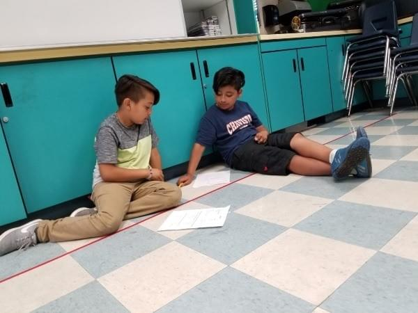 two boys work together on classroom floor