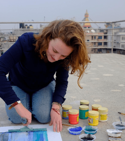 Emma painting her heart out with the Boudhanath Stupa in the background