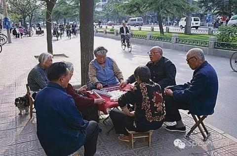 Full-Time Mahjong Gamblers in China during the spring. old people playing outside