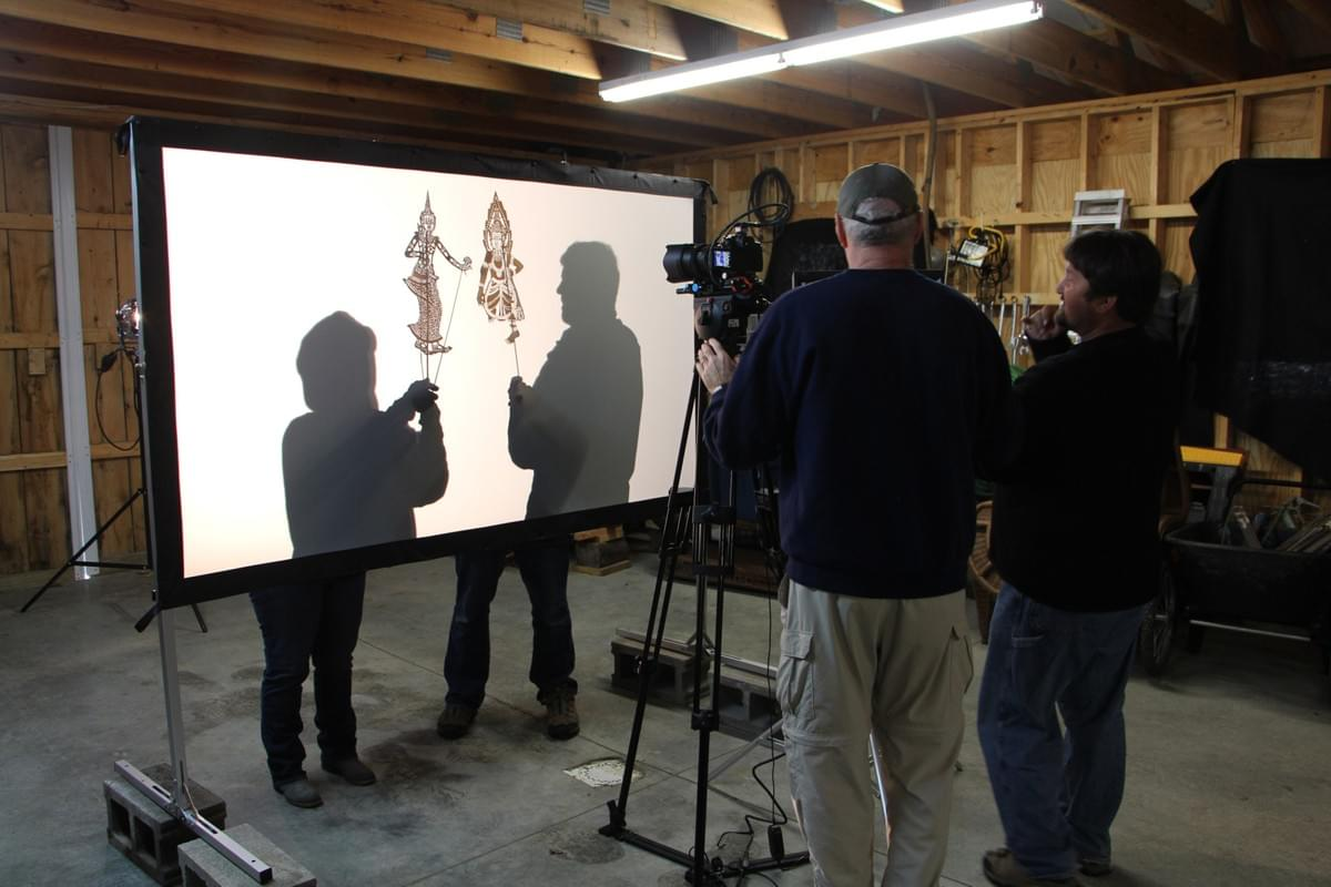 Videographer Peter Carroll & Puppet Director Scott Hitz test filming the shadow puppets. Behind screen: Lynda Thompson and Norm Scott