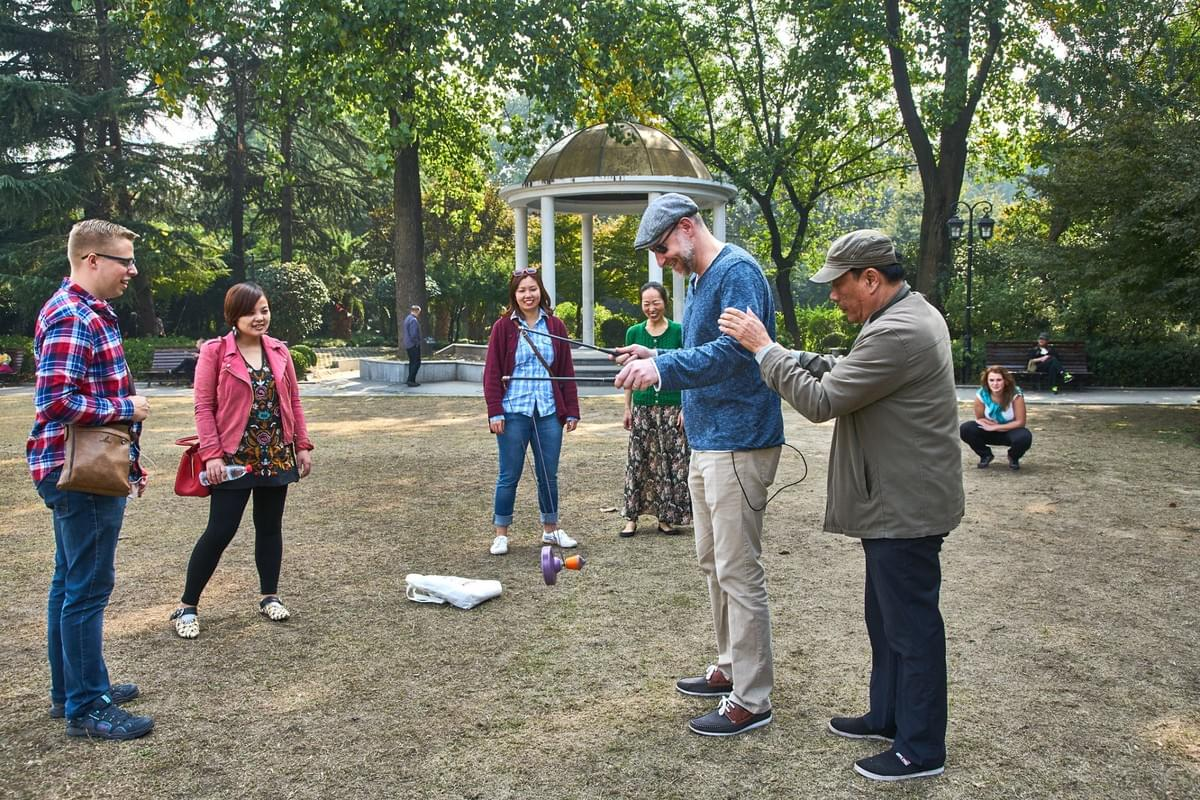 Picture source:Culutr Shock's private; local elderly teaching our Tour Participants how to play dǒu kōng zhú - Chinese yoyo; shot by Mathias Guillin