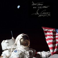 Apollo 17 Commander Gene Cernan posing next to the US Flag with Earth overhead.
